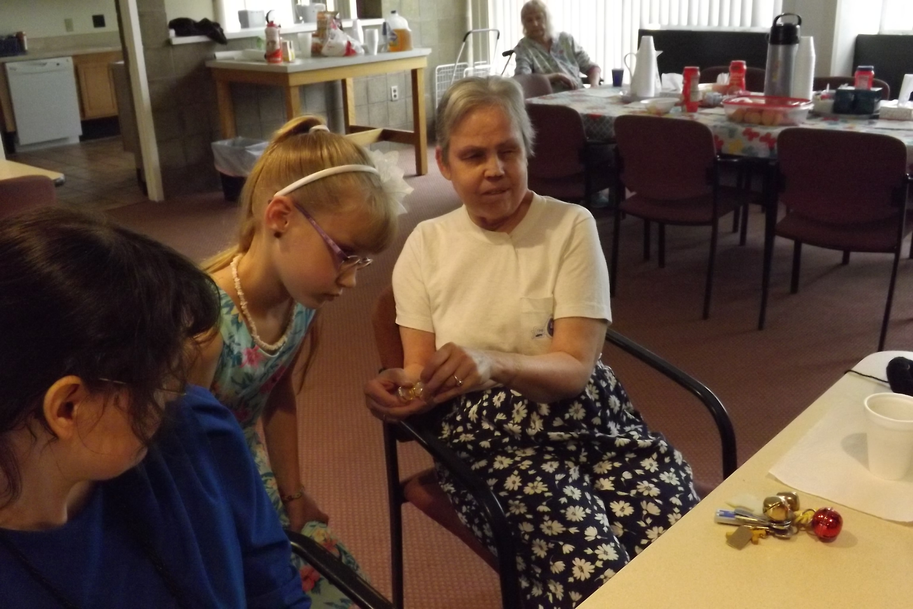 Kay shows her braille watch to Savannah at an Adaptive Life Skills Meeting.